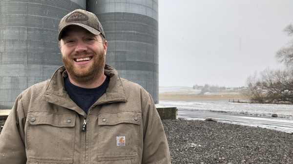 Allen Druffel, 34, of Colton, Wash., stands in front of the co-op silos that hold his unsold chickpeas. Last year he was getting 50 cents a pound for his pulse crop. Now, the going price is 18 cents a pound — well below his cost of production.