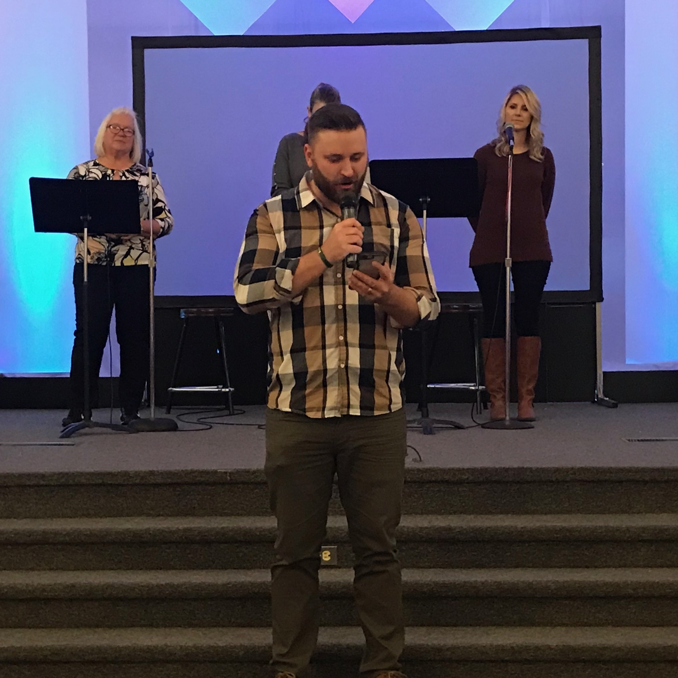 Youth pastor Kyle Smith of First Assembly of God Paradise reads from the Bible on his phone because his copy of the book burned in the Camp Fire. His congregation is one of several now worshiping with congregations in Chico.
