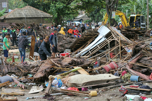 Residents inspect a house damaged by a tsunami, in Carita, Indonesia. The tsunami, which struck late Saturday, killed scores of people.