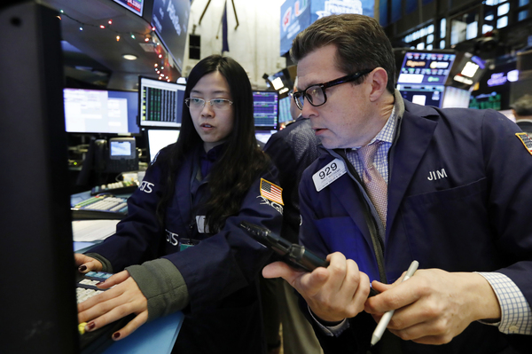 Specialist Vera Liu (left) and trader James Matthews work on the floor of the New York Stock Exchange on Wednesday. U.S. stocks are experiencing a post-Christmas rally after record-breaking losses on Monday.