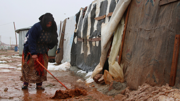 A Syrian refugee shovels mud in front of a makeshift shelter in an unofficial camp for Syrian refugees in Iaat in Lebanon