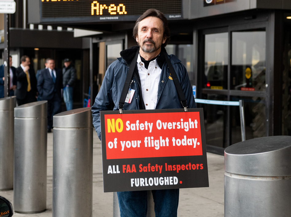 A man holds a placard at Newark Liberty International Airport on Tuesday, reminding travelers that FAA safety inspectors have been furloughed during the shutdown. (Michael Brochstein/SOPA Images/LightRocket via Getty Images)