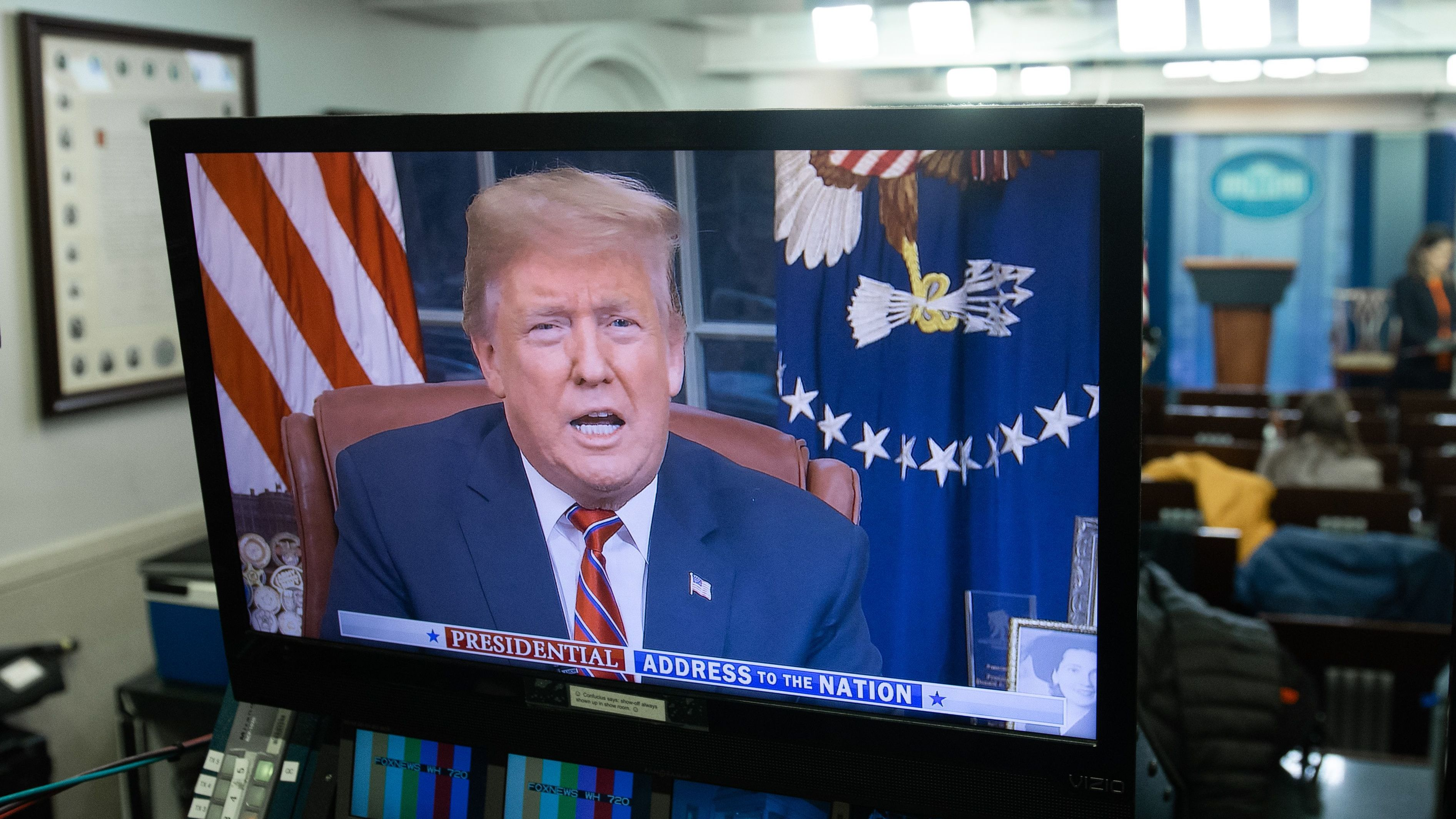 President Trump appears on a monitor in the Press Briefing Room of the White House on Tuesday.