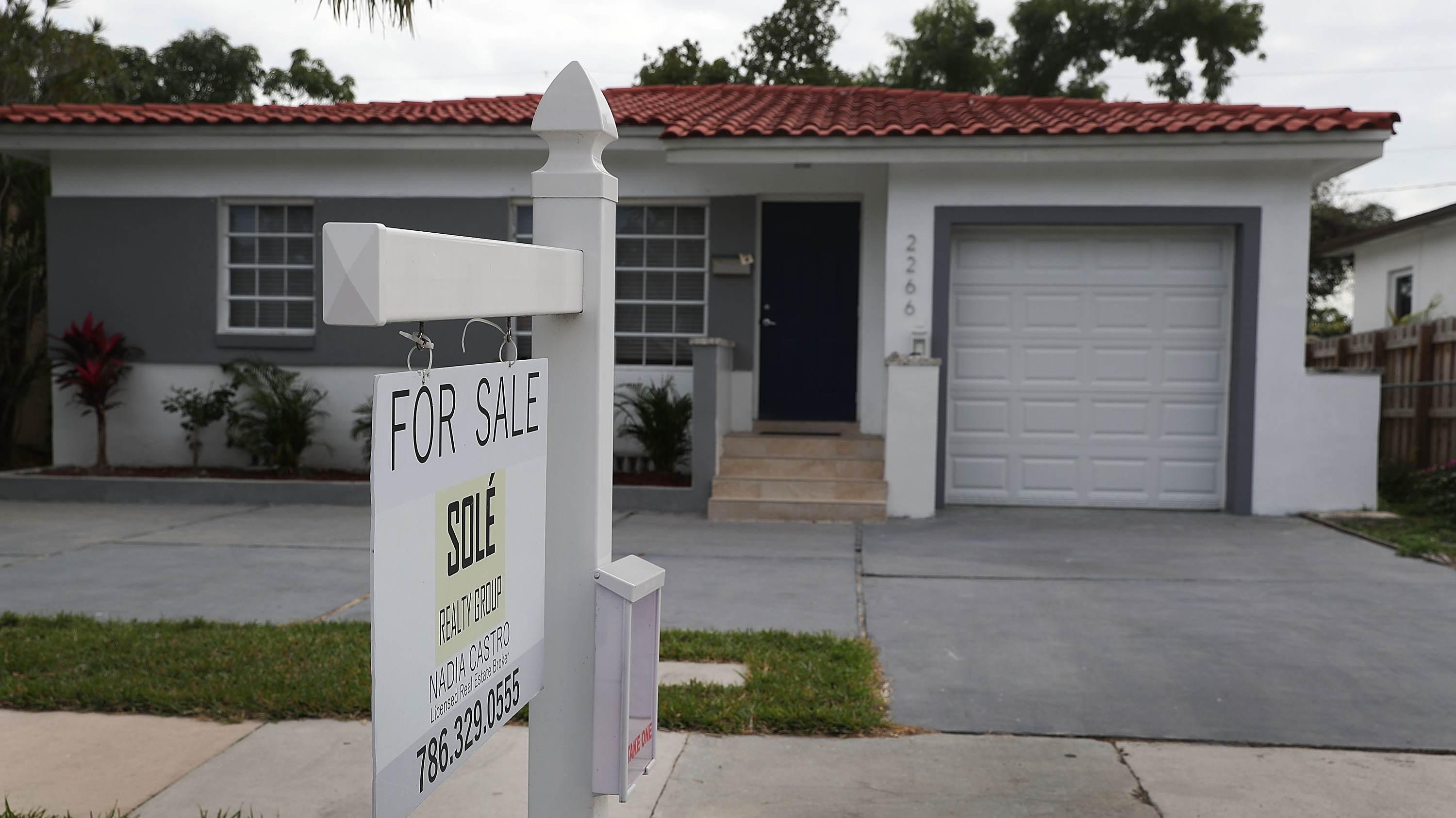 """A """"for sale"""" sign is seen in front of a home in Miami on Jan. 24, 2018. The partial shutdown of the federal government is causing some financial problems for furloughed workers who can't refinance their mortgages or buy homes because lenders can't verify their income."""
