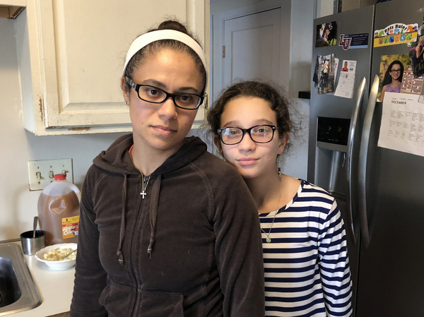 Rita Silva Martins and her 9-year-old daughter, Zaila, at home on a day off. Martins is working overtime, but worries she won't see a paycheck in time to pay her mortgage or day care bills, so she can keep her house and her job.