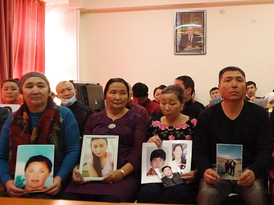 In this Dec. 7, 2018, relatives of people missing in China's far western region of Xinjiang hold up photos at an office of a Chinese Kazakh advocacy organization in Almaty, Kazakhstan.