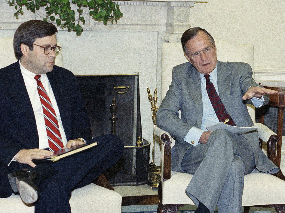 Then-Attorney General William Barr, left, with President George H.W. Bush. Barr supported Bush's pardons for six people caught up in the Iran-Contra scandal, which is resonating today. (Marcy Nighswander/AP)