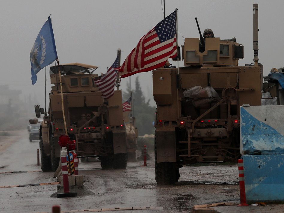 """The Pentagon has """"begun the process of our deliberate withdrawal from Syria,"""" a military spokesman says. In this photo from Dec. 30, 2018, a line of U.S. military vehicles are seen at a checkpoint in northern Syria. (Delil Souleiman /AFP/Getty Images)"""