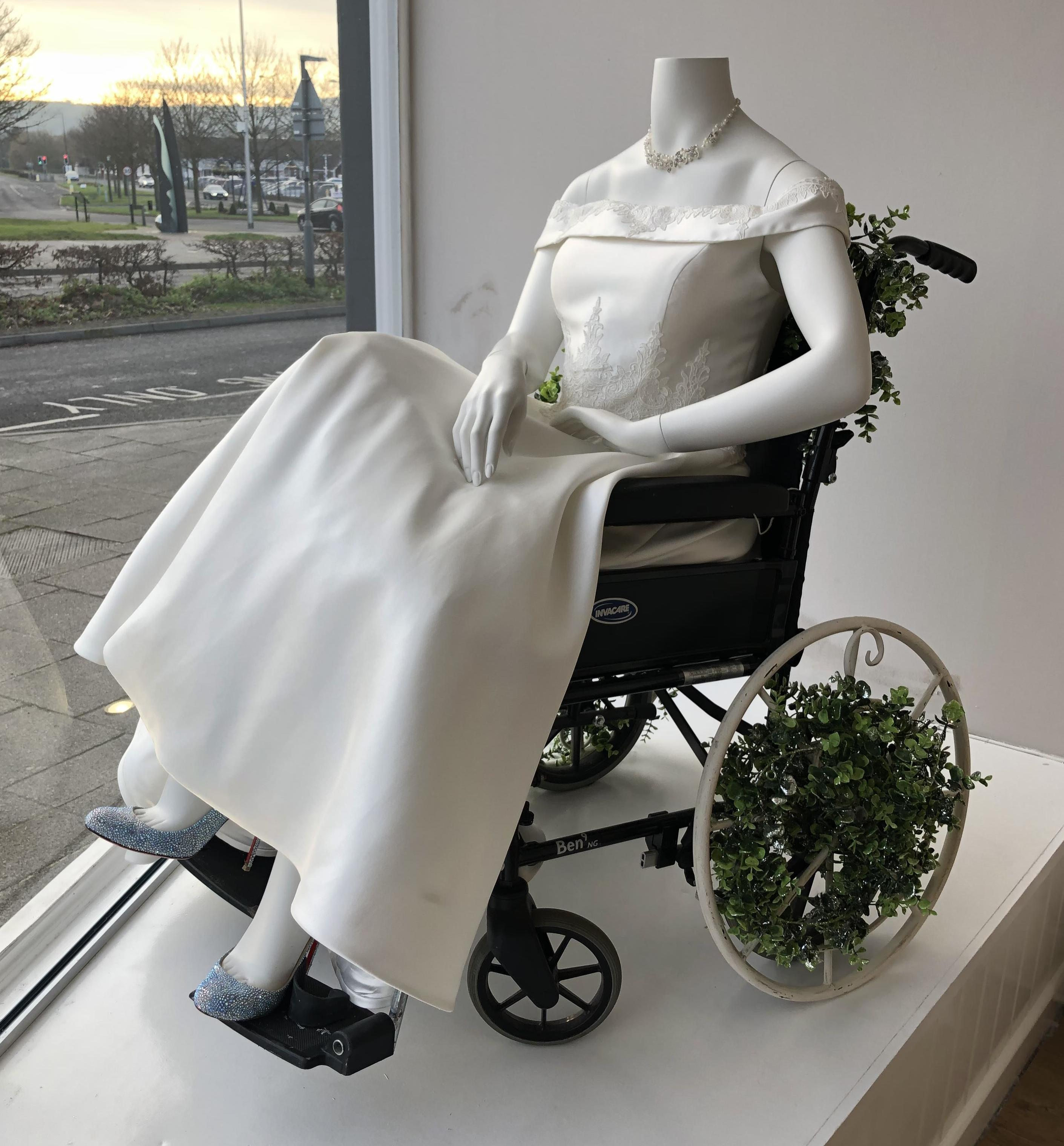 "Bridal shop co-owners have affectionately named their display mannequin sitting in a wheelchair ""Prunella."""