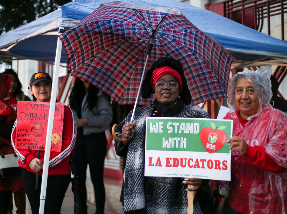 """Educators from Hollenbeck Middle School in Boyle Heights, Los Angeles chant, """"Teachers united will never be defeated!"""" in front of their school. (Roxanne Turpen for NPR)"""