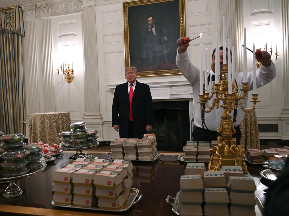 President Trump talks to the press about the table full of fast food laid out in the State Dining Room of the White House for a reception for the Clemson Tigers. (Susan Walsh/AP)