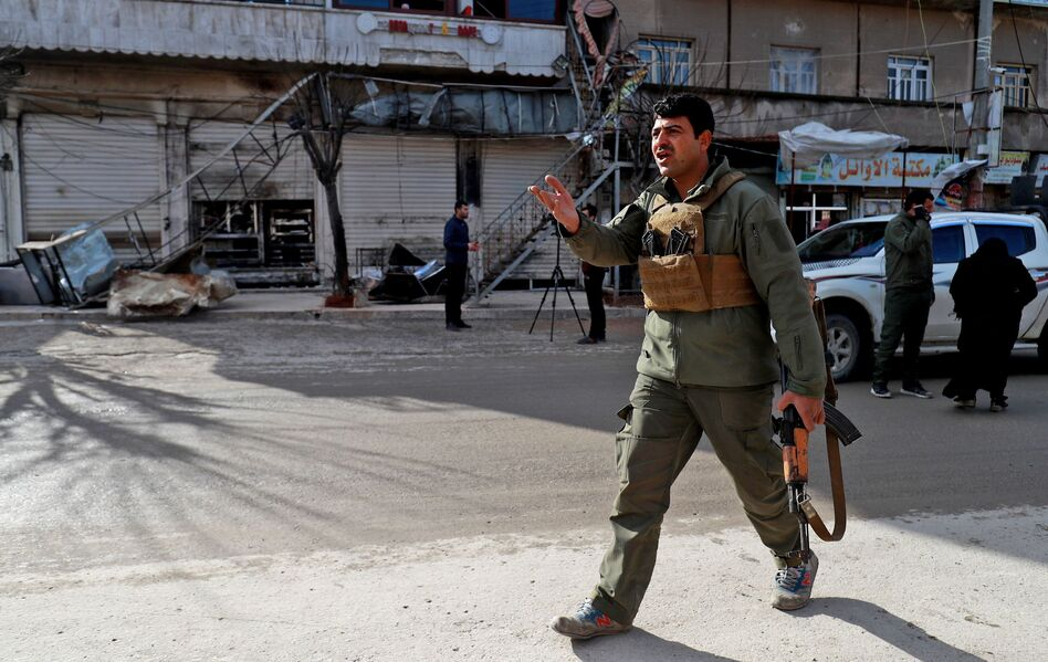 A security force member walks outside a shuttered restaurant Thursday in Manbij, Syria, the site of a suicide attack that killed more than a dozen people, including four Americans, a day earlier. The Islamic State claimed responsibility for the attack. (Delil Souleiman /AFP/Getty Images)