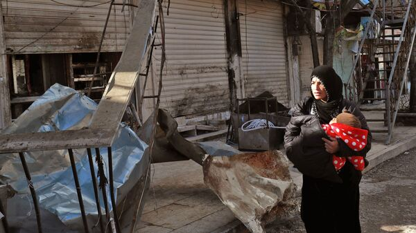 A Syrian woman carries an infant Thursday past the ruins of a restaurant in Manbij that was targeted by the Islamic State. Four Americans were killed in the attack.