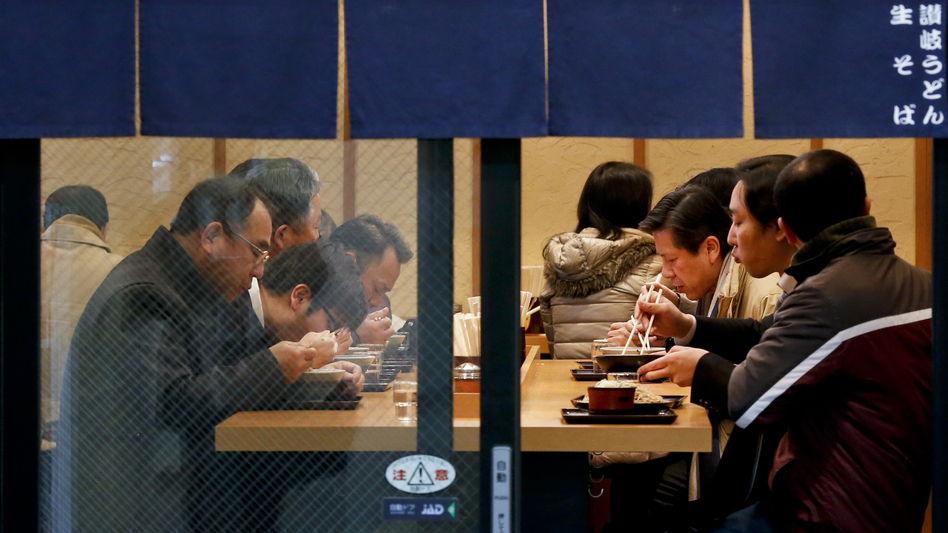 People slurp soup and pluck noodles at a soba and udon restaurant in Tokyo in February 2016.
