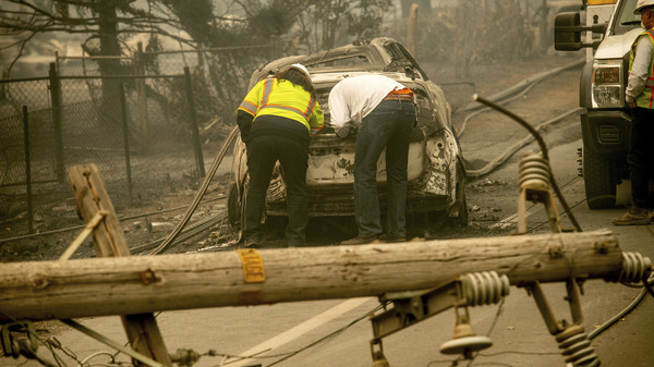 With a downed power utility pole in the foreground, residents of Paradise, Calif., examine a burned-out vehicle destroyed by last year