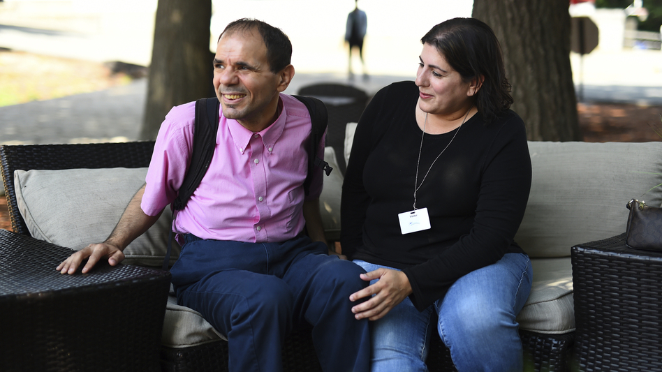 Angela Disisto of Medford, Mass., sits with her brother, Luigi, who has autism, at the Judge Rotenberg Educational Center in Canton, Mass. The backpack Luigi is wearing carries equipment that would give him a two-second electric skin shock if staff deem his behavior dangerous. (Meredith Nierman/WGBH News)