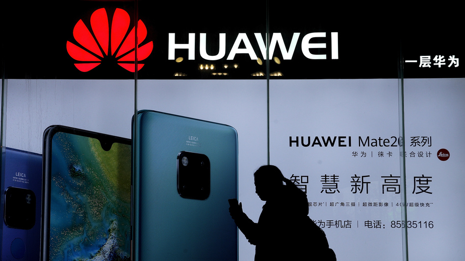 A woman browses her smartphone as she walks by a Huawei store at a shopping mall in Beijing. The telecom giant is at the center of a geopolitical feud between China and the United States. (Andy Wong/AP)