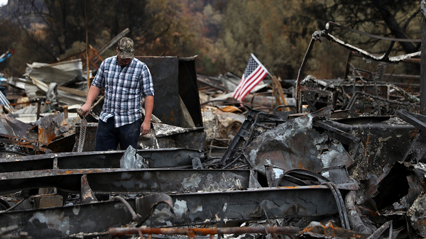 Noah Fisher looks over his home that was destroyed by the Camp Fire in November 2018 in Paradise, California. Investigators are examining whether PG&E power lines helped ignite the fire.