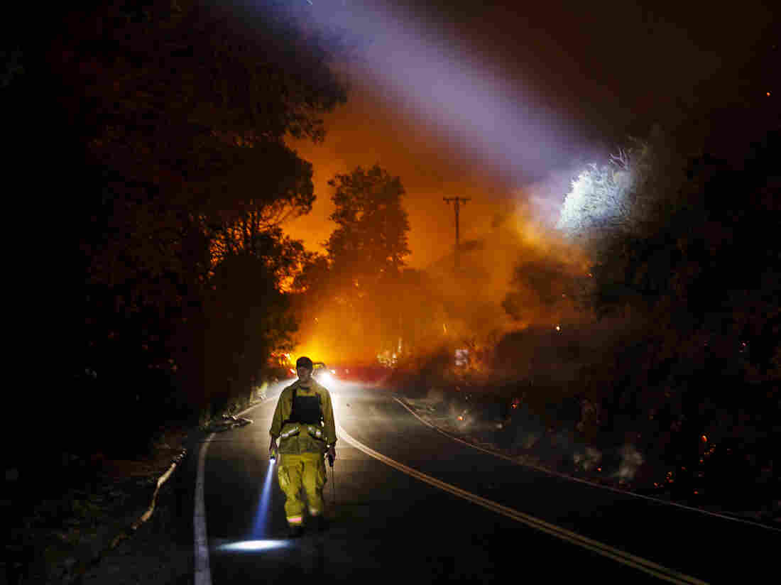 Firefighter points their beam lights around a burnt area to check for damages.