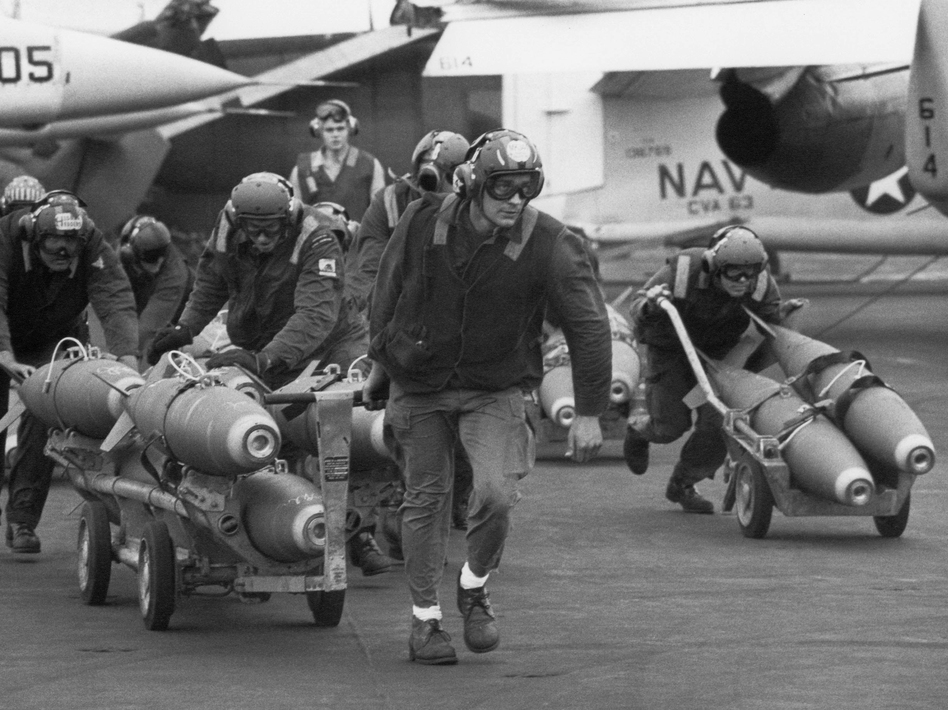 U.S. Navy armorers wheel out 500-pound bombs for the wing racks of jets aboard the aircraft carrier USS Kitty Hawk in March 1971 off the coast of Vietnam. (Rick Merron/AP)
