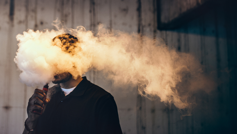 """""""There's a certain notion that e-cigarettes are harmless,"""" says Dr. Paul Ndunda, an assistant professor at the School of Medicine at the University of Kansas in Wichita. """"But ... while they're less harmful than normal cigarettes, their use still comes with risks."""" (RyanJLane/Getty Images)"""