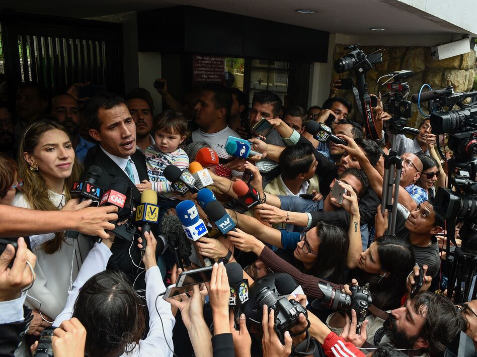 Opposition leader Juan Guaidó talks to the press as he holds his daughter, Miranda, next to his wife, Fabiana Rosales, outside his home in Caracas on Thursday. (Federico Parra/AFP/Getty Images)