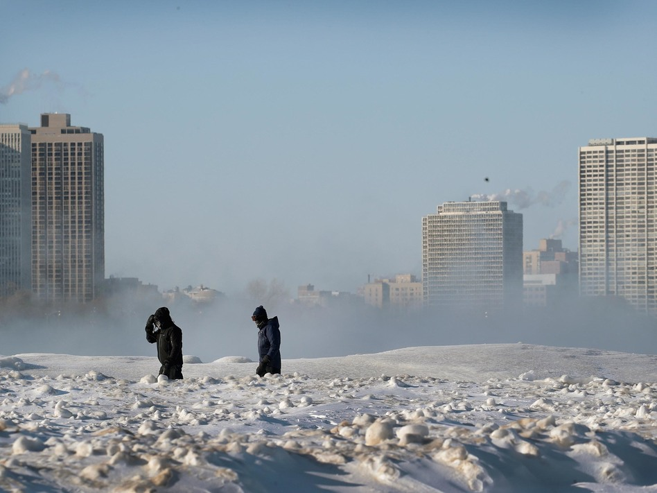 Bitterly cold temperatures continue to grip the Great Plains and Upper Midwest. People are seen here walking along the frozen lakefront on Wednesday in Chicago. (Scott Olson/Getty Images)
