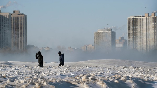 Bitterly cold temperatures continue to grip the Great Plains and Upper Midwest. People are seen here walking along the frozen lakefront on Wednesday in Chicago.