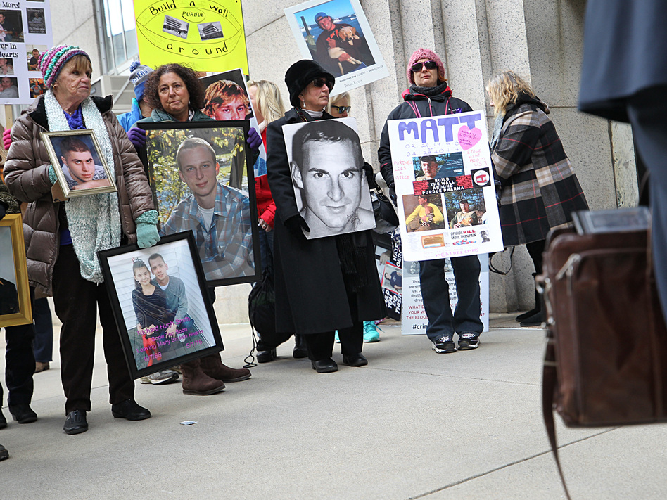 Families that lost loved ones to the opioid crisis protested outside Suffolk Superior Court in Boston as lawyers for Purdue Pharma entered the courthouse for a status update in the Massachusetts attorney general's suit against the company on Jan. 25. (Suzanne Kreiter/Boston Globe via Getty Images)