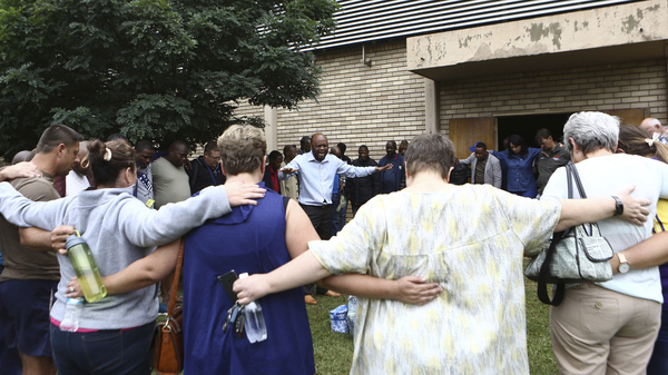 A pastor leads people in prayer Friday at the site of a walkway collapse at the Driehoek high school in Vanderbijlpark, South Africa.