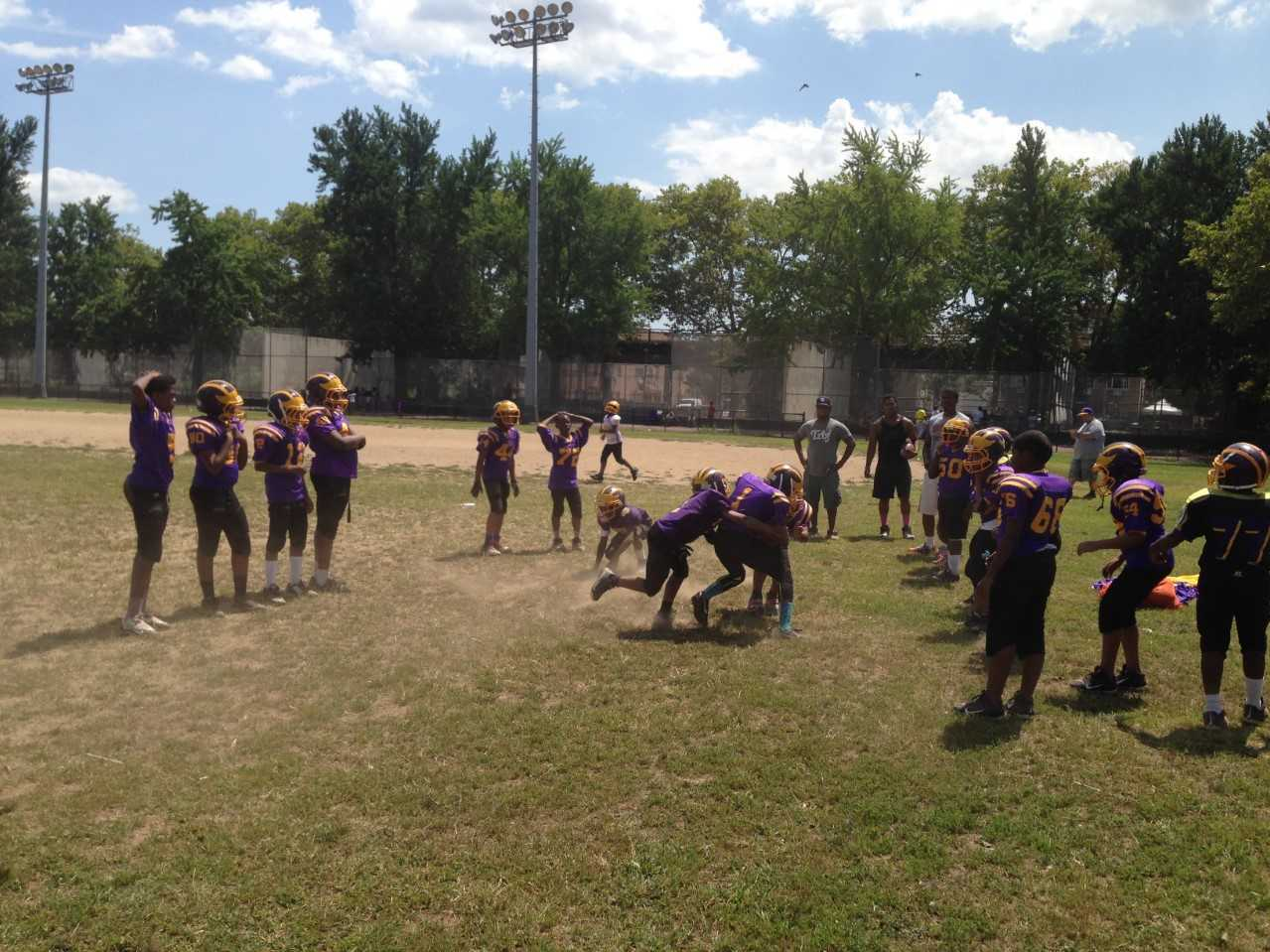 Boys on the Mo Better Jaguars Pee Wee football team collide during tackling drills on the first full-contact practice of the season in August 2014. (Courtesy of Albert Samaha)