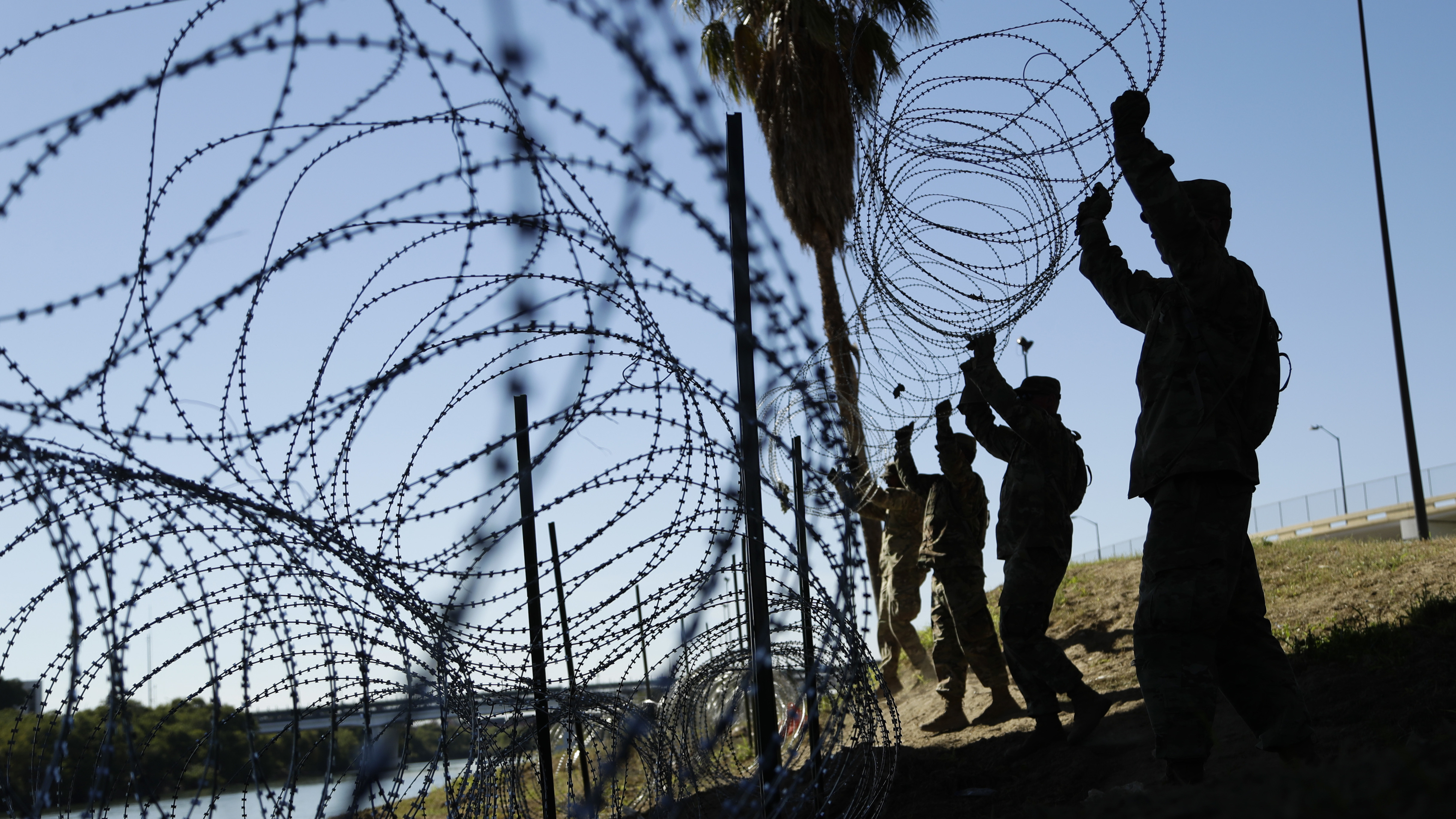 Members of the U.S. military install multiple tiers of concertina wire along the banks of the Rio Grande near the Juarez-Lincoln Bridge at the U.S.-Mexico border in Laredo, Texas, in November.
