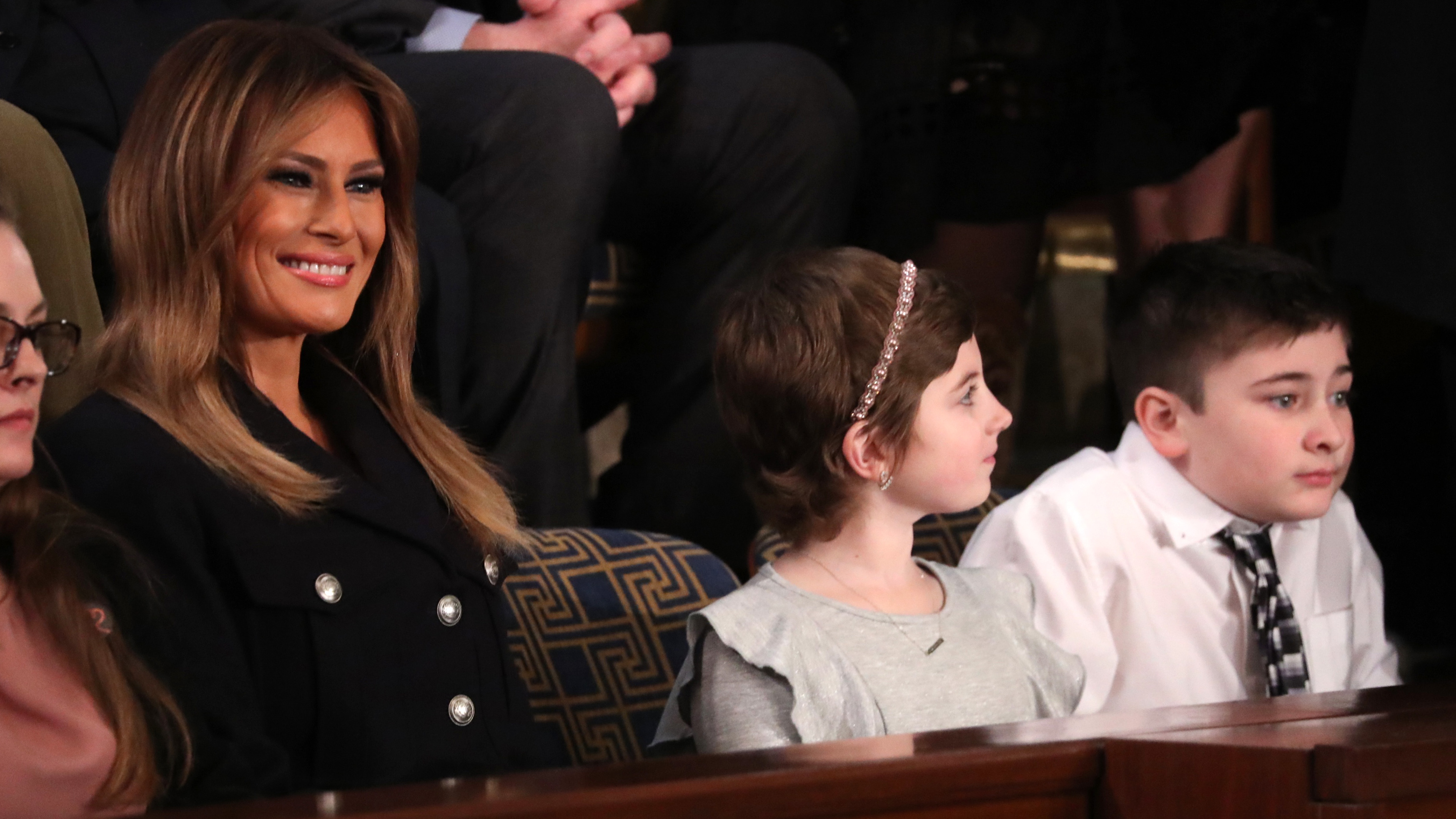The frst lady sits with guests Grace Eline (center), a cancer survivor, and Joshua Trump (right), a Delaware student who has been bullied because of his last name, during Tuesday's State of the Union address.