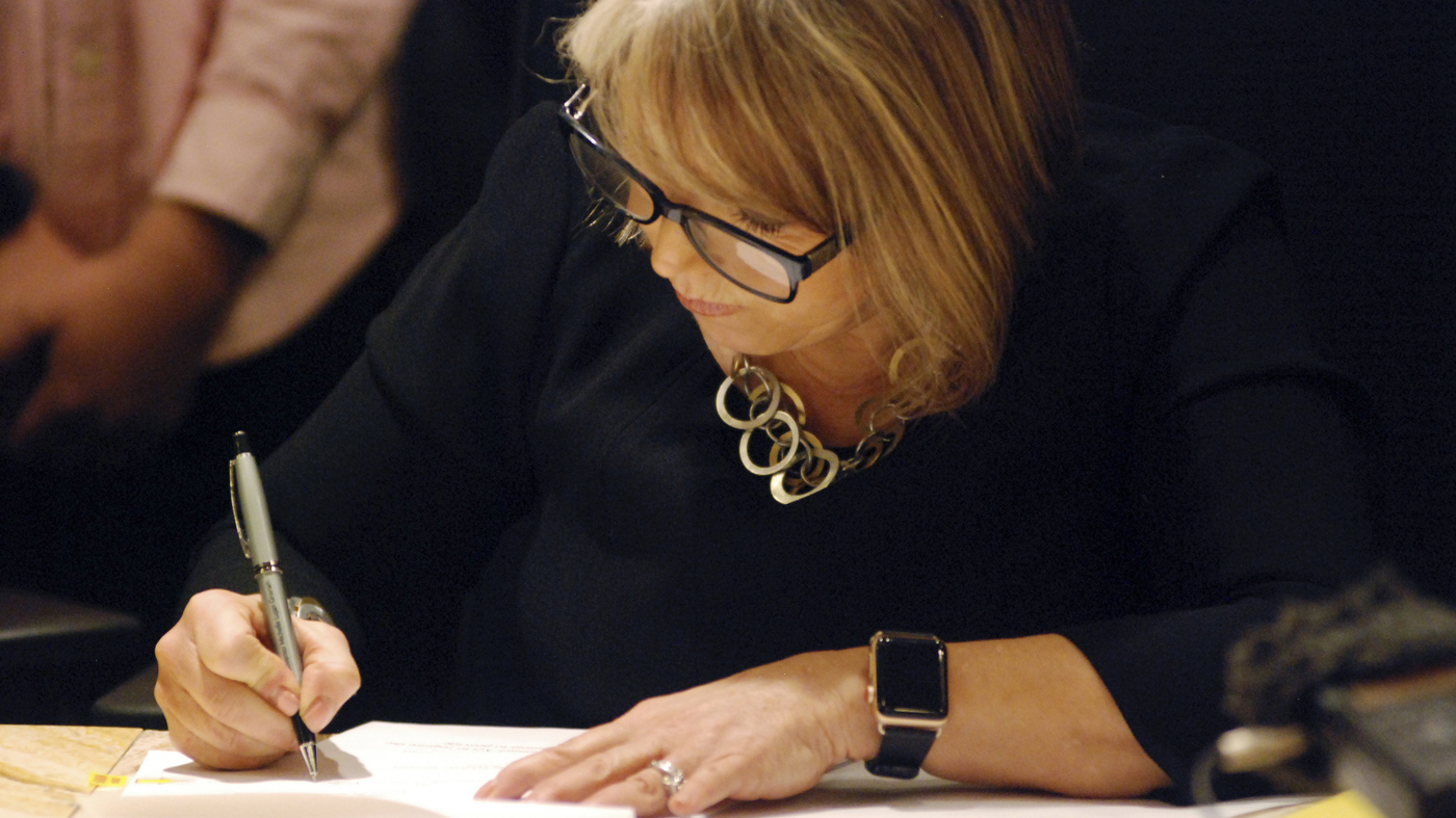 Photo of Gov. Michelle Lujan Grisham signing a piece of paper