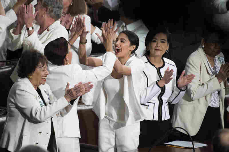 Reps. Alexandria Ocasio-Cortez, D-N.Y., right, high fives Nydia Velazquez, D-N.Y., as Democratic members celebrate in the House Chamber.