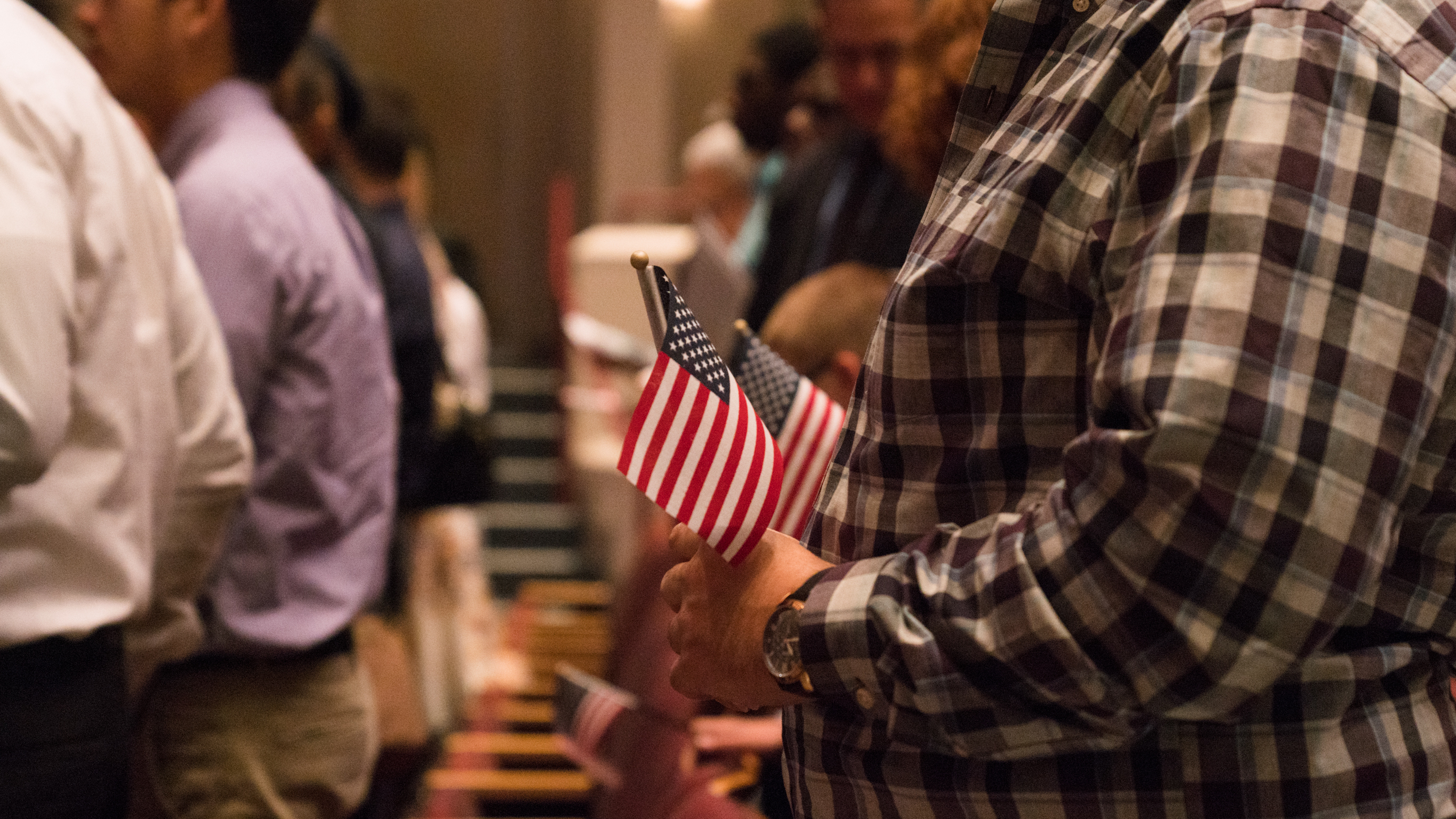 Newly sworn-in U.S. citizens rise from their seats during a 2018 naturalization ceremony in Alexandria, Va.