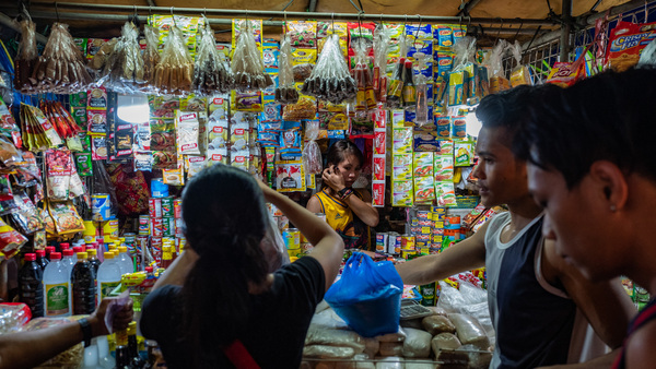 Singe-use plastic packets - containing everything from ketchup to shampoo — are hard to recycle because other materials are used to make them. Above: A vendor sells the packets in Manila, where they are known as sachets.