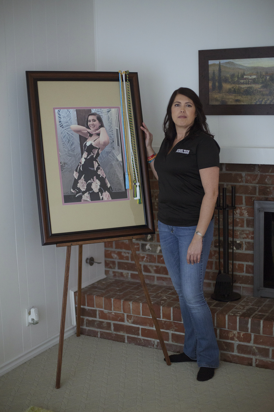 One year after Carmen's death, April Schentrup stands beside a photograph of her daughter that was used during her funeral but now rests in the family's new home. April, who worked as an elementary school principal near Parkland, Fla., now advocates for gun reform. (Alyse Young for NPR)