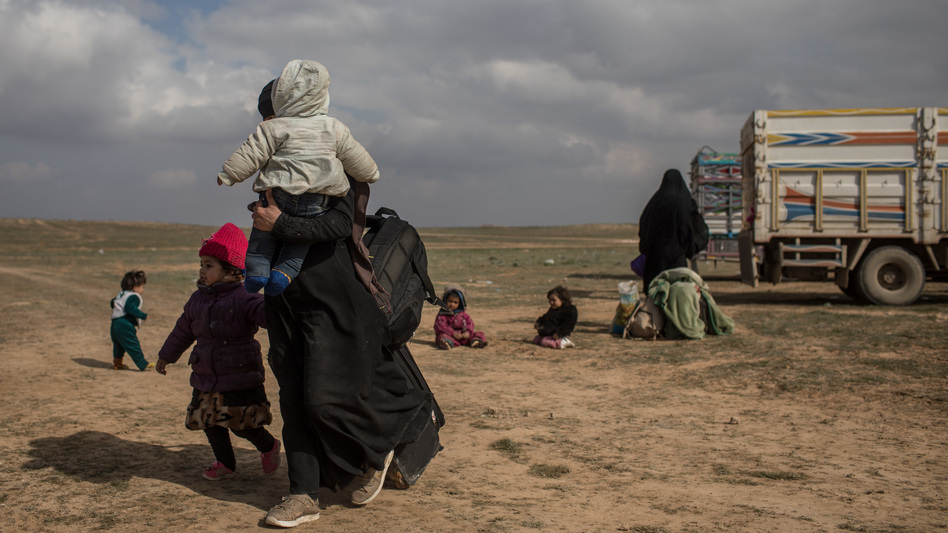 Civilians who have fled fighting in Bagouz wait to board trucks after being screened by members of the Syrian Democratic Forces (SDF) at a makeshift screening point in the desert on Saturday in Bagouz, Syria. After weeks of fighting the SDF announced the start of a final operation to oust ISIS from the last village held by the extremist group. (Chris McGrath/Getty Images)