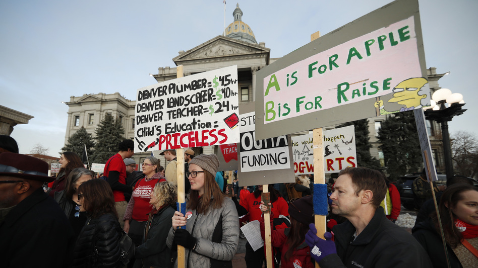 Denver teachers carry placards as they wait to march after a rally in support of a strike outside the state Capitol last month. Denver schoolteachers are going on strike over how their base pay is calculated.
