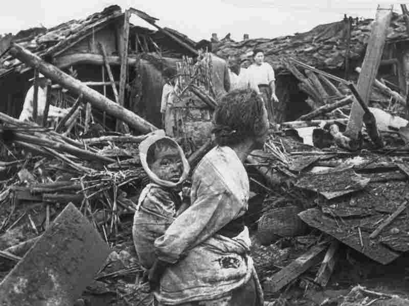 A woman and her grandchild wander among the debris of their wrecked home in the aftermath of an air raid by U.S. planes over Pyongyang in 1950.
