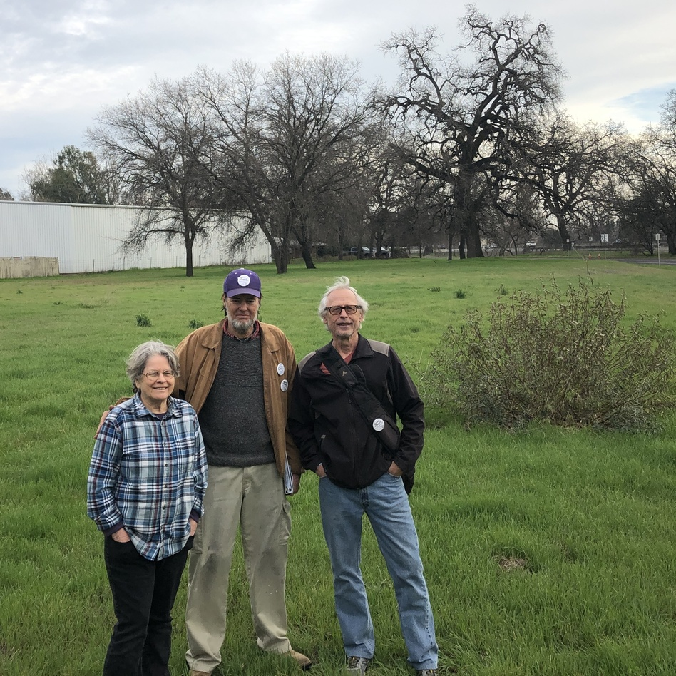 Chico Housing Action Team organizers Leslie Johnson, left, Charles Withuhn, center, and Bill Kurnizki, right, in the field in south Chico where they plan to soon break ground on a 33-unit tiny home community for homeless adults called Simplicity Village. (Eric Westervelt/NPR)
