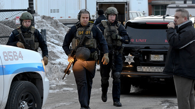 Police officers respond to a shooting in Aurora, Ill., Friday afternoon. A gunman killed five people, then wounded five police officers in a firefight.