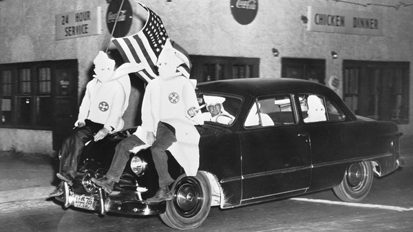In 1949, Ku Klux Klan members ride down a street in Gadsden, Ala., as part of an 18-car parade.