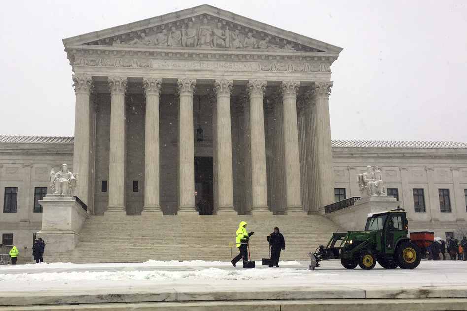 Crews remove early morning snow during a winter storm at the Supreme Court on Wednesday. It's not unusual for the high court to be open when the rest of Washington is closed. (Jessica Gresko/AP)