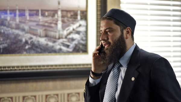 Hassan Shibly, attorney for the family of Hoda Muthana, speaks on a phone before a news conference Wednesday.