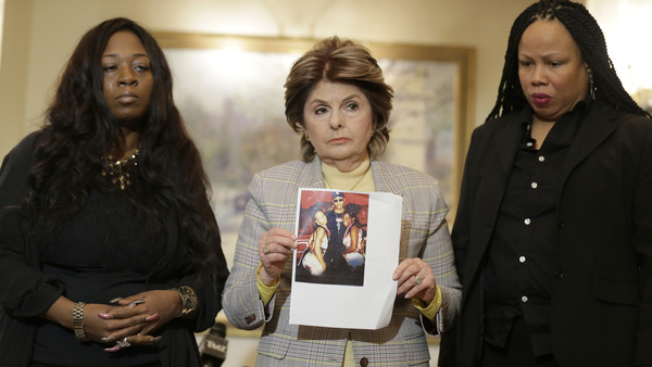 Rochelle Washington (left) and Latresa Scaff (right) look on Thursday in New York City, as attorney Gloria Allred holds up a picture of them as teenagers on the night R. Kelly allegedly made sexual advances on them.
