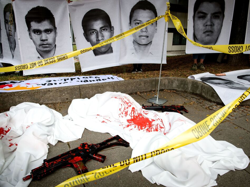 German demonstrators used crime scene tape and replica guns to draw attention to a trial over Heckler & Koch's deal that sent G36 rifles to several Mexican states that were under a ban. The company was ordered to pay a large fine on Thursday. The photos above show images of Mexican students believed to have been killed with the weapons. (Sina Schuldt /AFP/Getty Images)