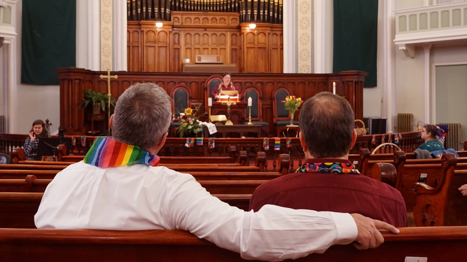 Daron Smith, left, and his husband, Chris Finley, right, worship at a Sunday morning service at Lafayette Park United Methodist Church in St. Louis, Mo. Smith, a lifelong United Methodist, said he feels hopeful ahead of a vote on LGBTQ ordination and same-sex weddings in the church. (Shahla Farzan/St. Louis Public Radio)