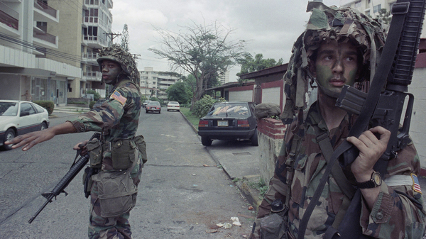 U.S. soldiers direct traffic outside the residence of the Peruvian ambassador to Panama, right rear, in Panama City, on Jan. 9, 1990. In December 1989, U.S. President George H.W. Bush sent thousands of troops to Panama to arrest the country